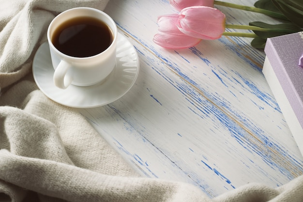 Pink tulips, white scarf, coffee cup and gift box on a white wooden surface