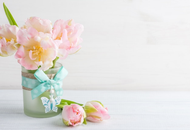 Pink tulips on a white wooden background