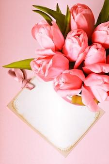 カードのクローズアップとピンクのチューリップ