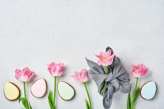 회색 배경에 행에 있는 부활절 진저 브레드 계란이 있는 핑크 튤립. 꽃무늬