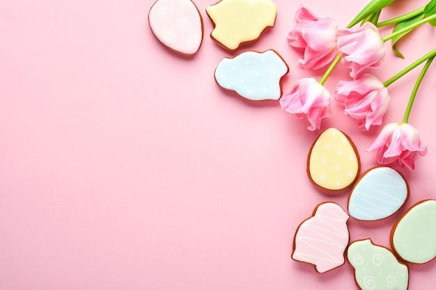 분홍색 배경에 행에 있는 부활절 진저브레드 달걀이 있는 분홍색 튤립. 꽃 패턴입니다. 조롱 및 배너. 텍스트를 위한 공간입니다.