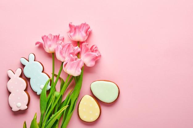 분홍색 배경에 줄지어 있는 부활절 진저브레드 달걀이 있는 분홍색 튤립