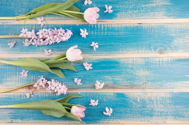 Pink tulips with flowers on wooden table