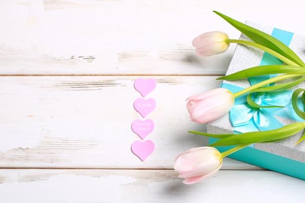 Розовые тюльпаны с подарочной коробкой на белой деревянной предпосылке. валентина день романтический фон.