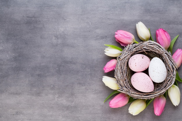 Розовые тюльпаны с розовыми яйцами гнездятся на сером столе
