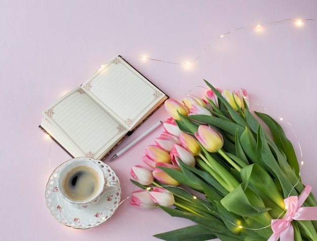 Pink tulips with a pink tape, a cup of coffee and a notebook with a pen