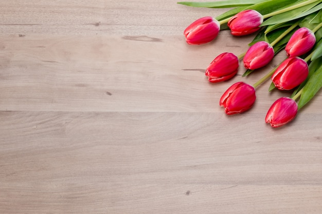 Pink tulips on wooden background with empty space