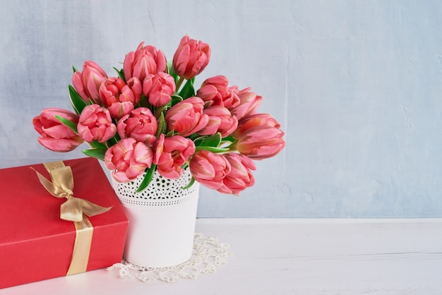 Pink tulups bouquet and red gift box. valentine's day, birthday or mother's day concept. copy space