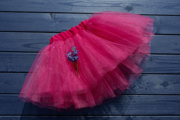 Pink tutu skirt for girl on blue wooden background.