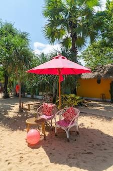 Розовый зонтик и стул на тропическом пляже