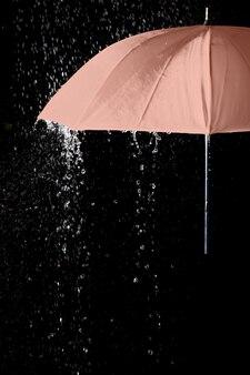 黒の背景と雨滴の下のピンクの傘。ビジネスとファッションのコンセプト。