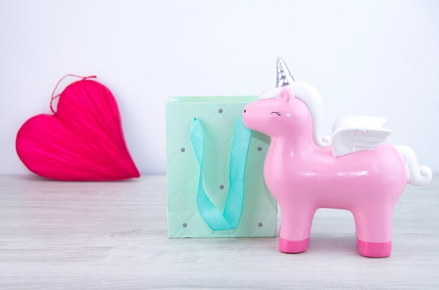 The pink unicorn toy stands next to the gift bag. selective focus . red heart in the background. gift to a girl.