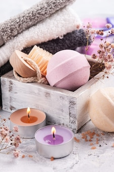 Pink vanilla aroma bath bombs in spa arrengement with dry flowers and lit candle