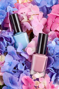 Of pink varnish on the bed of hortensia. fashion beauty concept in trendy pastel colors