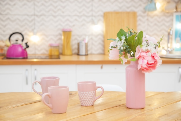 스칸디나비아 스타일의 밝은 주방에있는 테이블에 차를위한 꽃과 머그잔이있는 핑크색 꽃병.