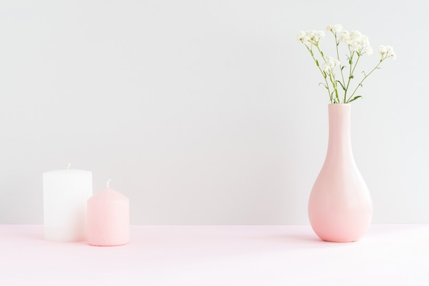 Pink vase with gypsophila and two candles on a pink table with copy space