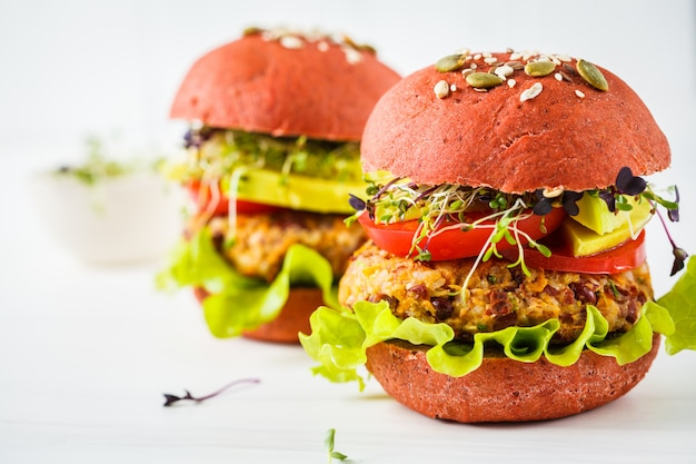 Pink vegan burgers with beans cutlet, avocado and sprouts on white
