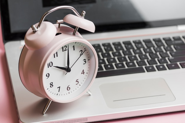 Pink vintage alarm clock on an open laptop