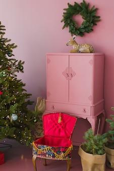 Розовый винтажный комод, новогодняя елка и венок над комодом, статуэтка оленя