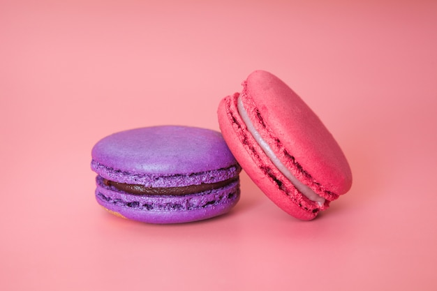 Pink and violet macaroons on a fashionable coral background close-up