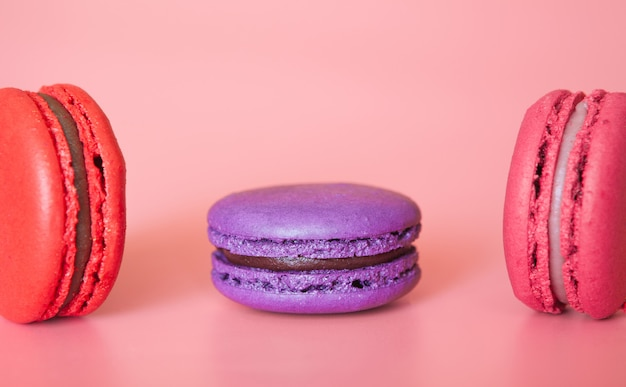 Pink and violet macaroons on a fashionable coral background