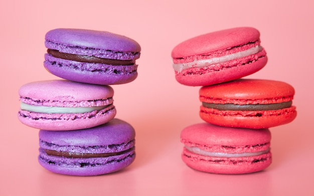 Pink and violet macaroons in a stack on a fashionable coral background close-up