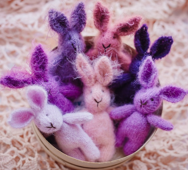 Pink and violet rabbits made of wool lie on tha basket