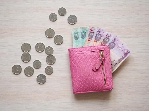 테이블에 아랍어 디르함과 핑크색 지갑