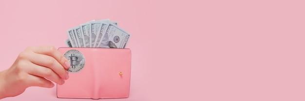 Розовый кошелек с долларами и биткойнами в женской руке на розовом с копией пространства.