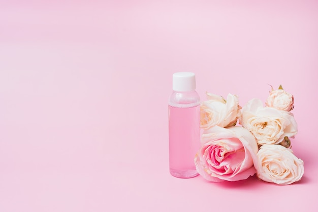 Pink water with rose extracts on a background of flower with copy space