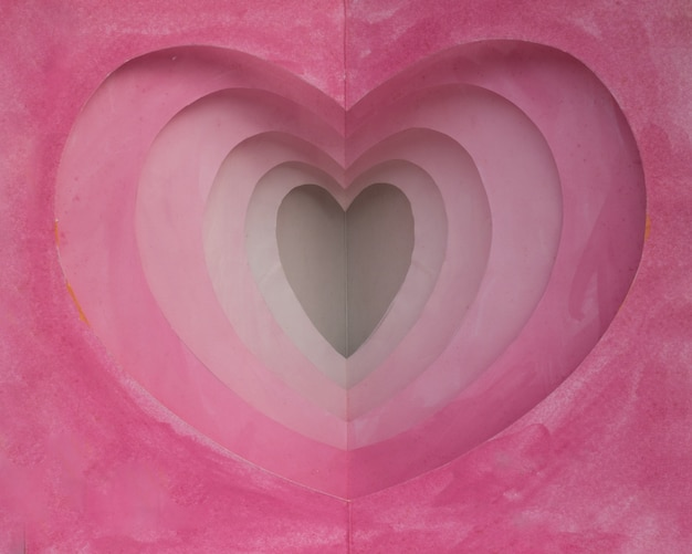 Pink watercolor card from paper cut into heart shape in many layers for background or deco