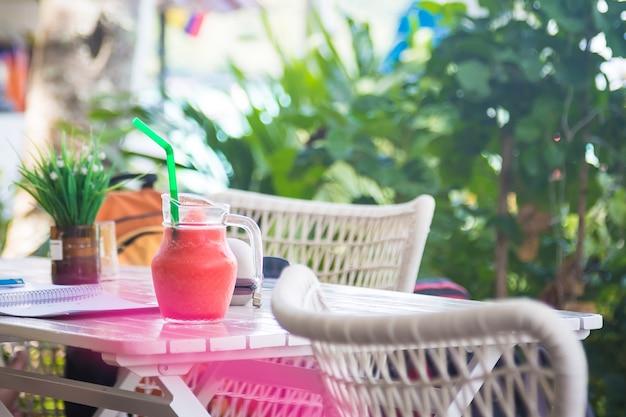 화창한 날에 짚이 달린 주전자에 있는 나무 테이블에 있는 열대 과일에서 나온 분홍색 수박 스무디