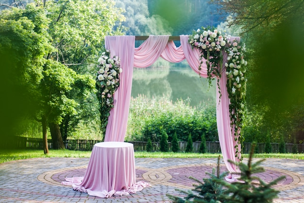 Pink wedding arch with floral white and pink decorations outside in summer