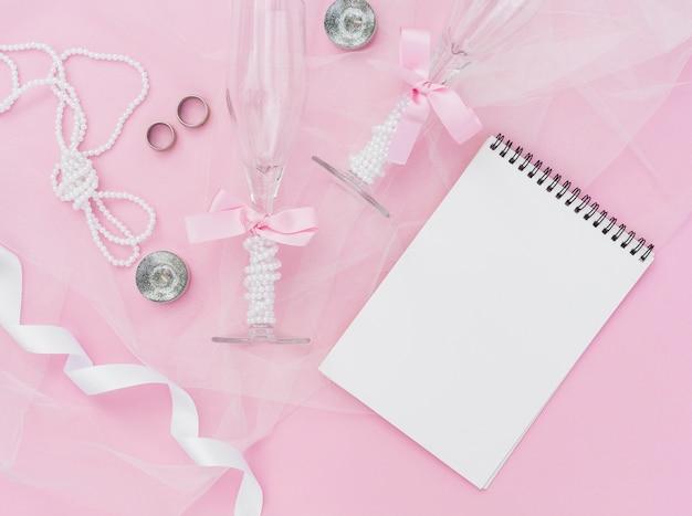 Decorazione di nozze rosa con blocco note vuoto