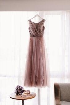 말린 꽃의 신부 부케와 창 배경에 핑크 웨딩 드레스