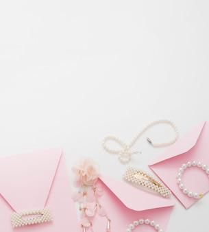 Pink wedding invitations are decorated with jewelry for the bride, with copy space.