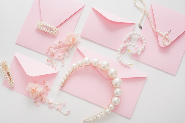 Pink wedding invitations are decorated with jewelry for the bride.