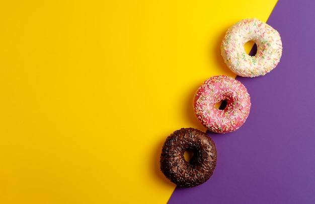 Розовые пончики из белого и черного шоколада на желтом и фиолетовом темно-фиолетовом фоне с копией пространства