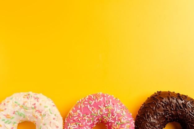黄色の背景にピンクの白と黒のチョコレートドーナツ上面図コピースペース