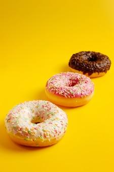 Розовые пончики из белого и черного шоколада на желтом фоне