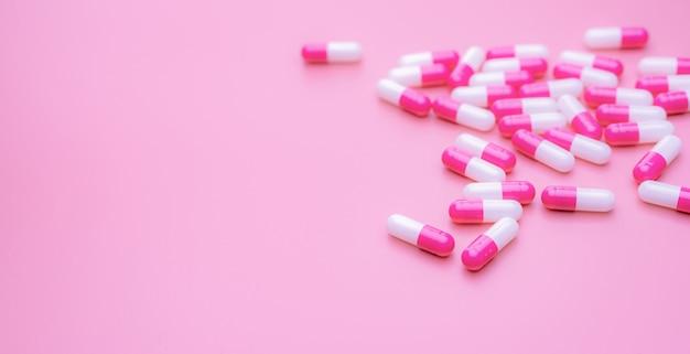 ピンクの表面に広がるピンクホワイトの抗生物質カプセルピル