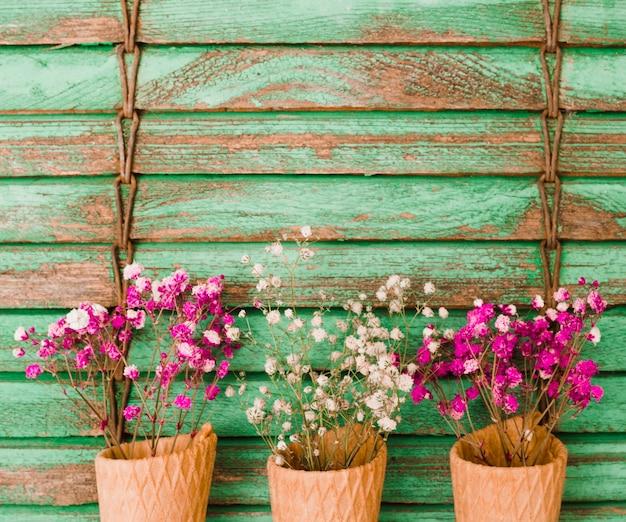 Fiori rosa e bianchi del baby-breath nel cono contro il contesto di legno
