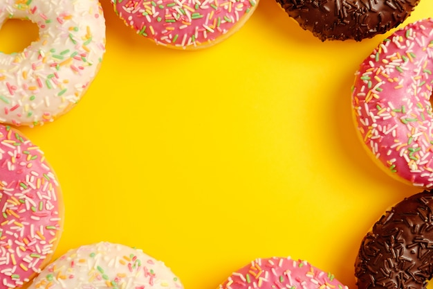Pink white and black chocolate donuts on yellow wall top view copy space