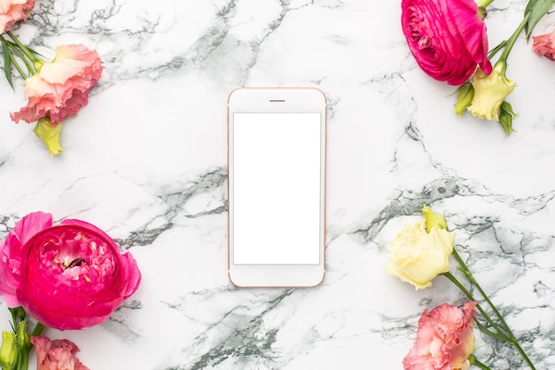 Pink and white flower bouquet with mobile phone on marble background with copyspace
