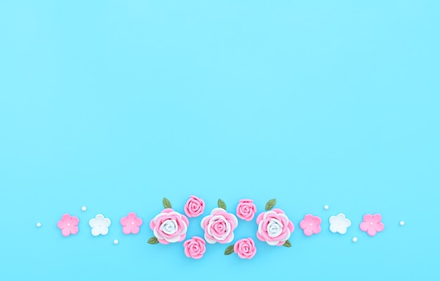 Pink and white flowers made of foamiran with green leaves and white beads on blue background.