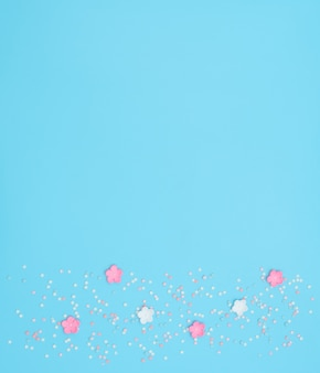 Pink and white flowers made of foamiran with star shaped confetti on blue.