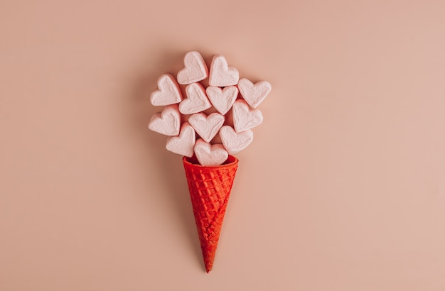 Pink and white heart shaped marshmallows with waffle cone on pink background. top view. copy space