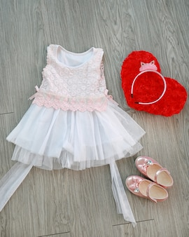Pink-white lace dress with girl's small shoes and red pillow on a wooden background