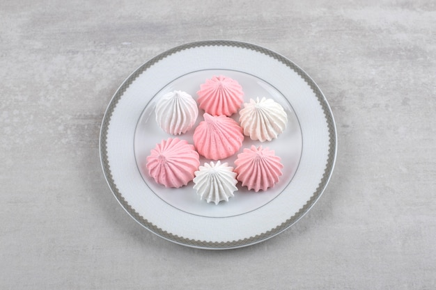 Pink and white meringue on a plate, on the marble.