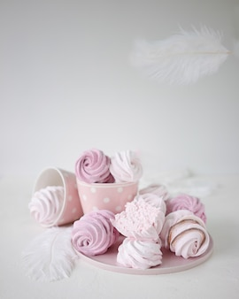 Pink and white meringues on white background. flying white feather